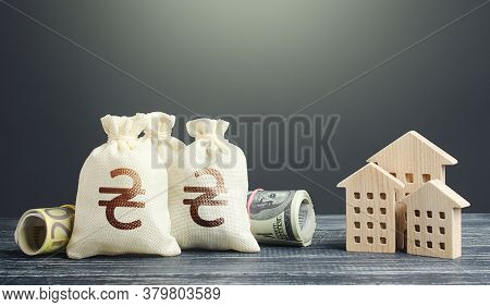 Ukrainian Hryvnia Money Bags And Residential Buildings Figures. Investments In Real Estate. Municipa