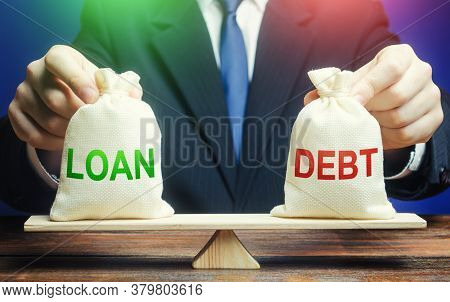 A Businessman Holds Bags With A Loan And Debt On Scales. Financial System Balance Difficulties. Borr