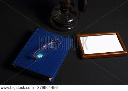 A Stack Of Old Books, A Oil Lamp, Empty Frame And Glasses On A Dark Background. Library At Night