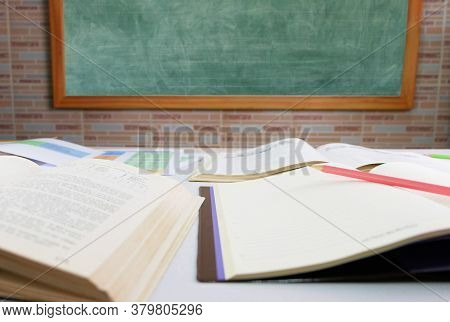 Pencil On Notebook With Blurred Textbooks On Table In Front Of Blackboard In Classroom