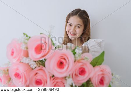 Asian Woman Wearing Orthodontic Silicone Trainer Sending Flowers To Camera And Smiling Look At Camer