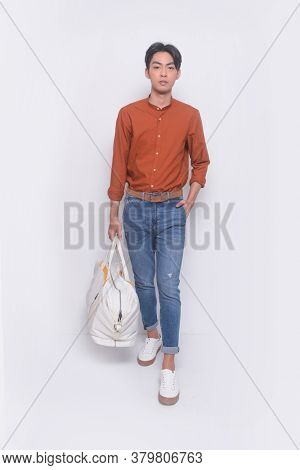 Full body Young handsome man with wearing brown shirt with holding handbag ,hat with blue jeans pants runway, in studio