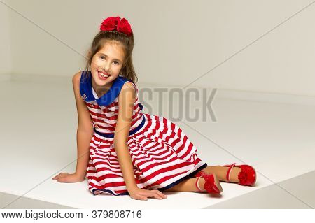 Beautiful Little Girl Sits In A Studio On A White Podium. Style And Fashion Concept.