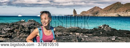 Panoramic banner of Galapagos tourist walking on Santiago Island in Galapagos Islands. Pinnacle Rock and Bartolome Island in background. Famous Galapagos cruise ship tour destination.