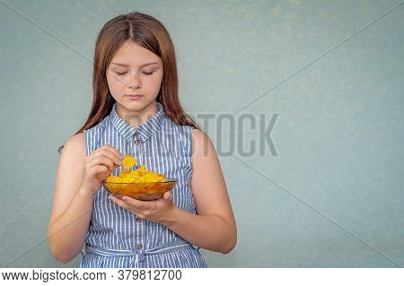 A Young Girl Holds A Plate Of Chips In Her Hand, A Chip In Her Other Hand And Looks At Her, Deciding