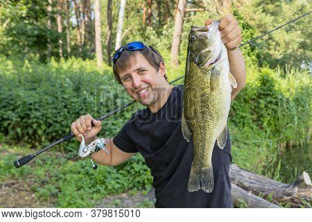 Bass Fishing. Fisherman Holding Largemouth Perch Fish