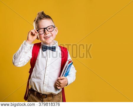 Happy Little Boy In Glasses With Books And Bag On His First Day To School. Funny Child Against Yello