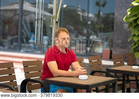 Serious Blond Man In Casual Style Red T-shirt Sit In Modern Cafe, Nervous Waiting Someone Or Changes