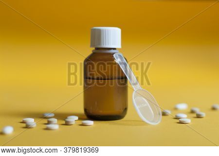 Cough Syrup. Cold Medicine. Pills And Medicine On A Yellow Background. Pharmaceutical Preparations F