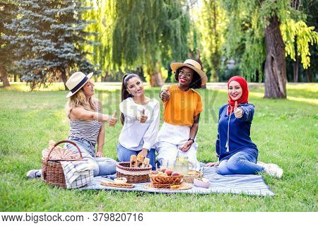 Young Multiracial Women Are On Picnic In The Park. Best Multiracial Friends Thumbs Up.