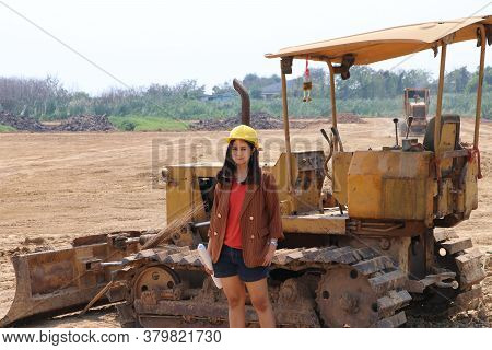 Female Civil Engineer Or Architect Wear The Yellow Helmet Standing On Background Of Front Loader Eng