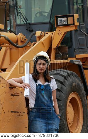 Female Civil Engineer Or Architect With White Helmet And Project Drafts While In Hand Standing With