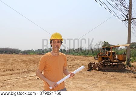 Male Civil Engineer Or Architect Wear Yellow Helmet And Project Drafts While In Hand Standing On Bac