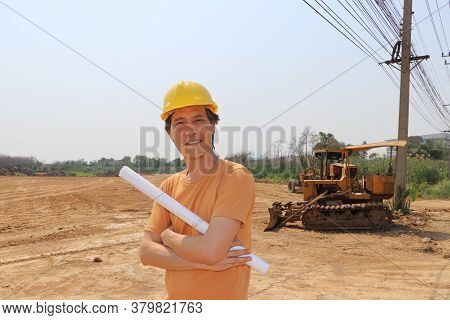 Male Civil Engineer Or Architect Wear The Yellow Helmet And Cross One Arm With Project Drafts While