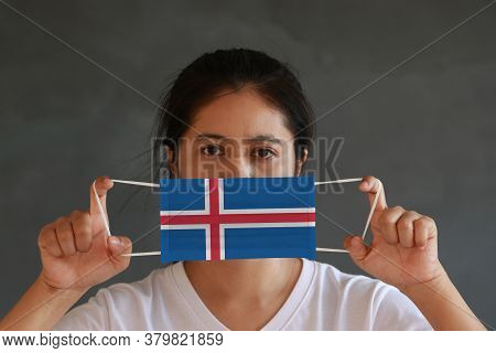 A Woman In White Shirt With Iceland Flag On Hygienic Mask In Her Hand And Lifted Up The Front Face O