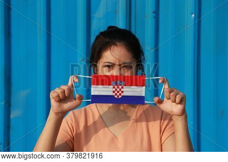 A Woman With Croatia Flag On Hygienic Mask In Her Hand And Lifted Up The Front Face On Blue Backgrou