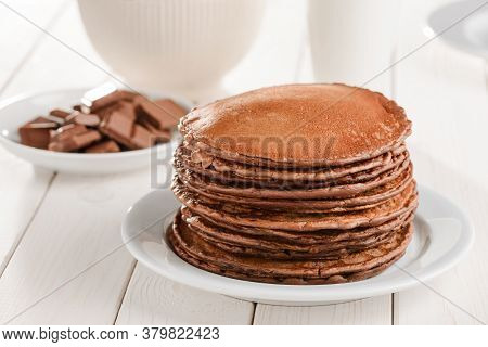 Pile Of Freshly Baked Pancakes, Chocolate Pieces And Milk On White Table