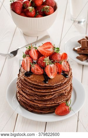 Pancakes With Strawberries And Chocolate Topping On White Table