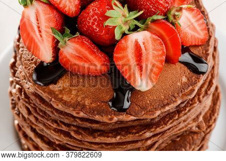 Brown Pancakes With Chocolate Syrup And Fresh Strawberries