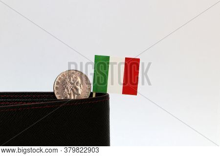 One Coin Of Italy Lire Money And Mini Italy Flag Stick On The Black Wallet With White Background. Re