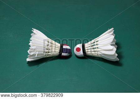 Two Used Shuttlecocks On Green Floor Of Badminton Court With Both Head Each Other. One Head Painted