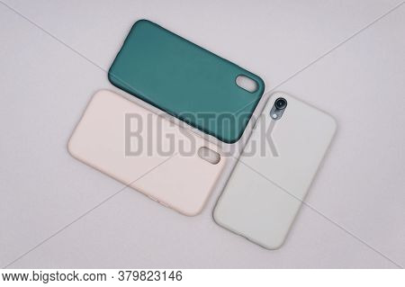 Grey, Green And Pink Smartphone Cases. Smartphone In A Gray Silicone Case. Protective Covers For The