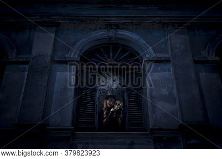 Halloween Witch Holding A Skull Standing In Old Damaged Window With Wall Over Cross, Church, Birds,