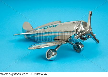 Metal Vintage Aircraft Toy, With Front Propeller. Retro Toy On Blue Background