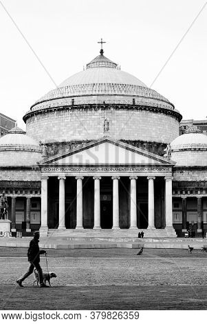 NAPLES, ITALY - GENUARY 04, 2008: image black and white people crosses Square Plebiscito in front of the Pantheon in Naples landmark and monument examples of neoclassical architecture in Italy