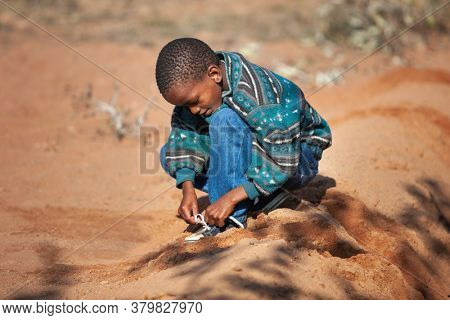 african child learning to tighten his shoe laces in the village sand
