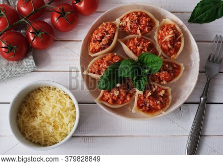 Italian Pasta Conchiglioni  Stuffed With Bolognese Sauce And Sprinkled With Cheese On White Wooden T