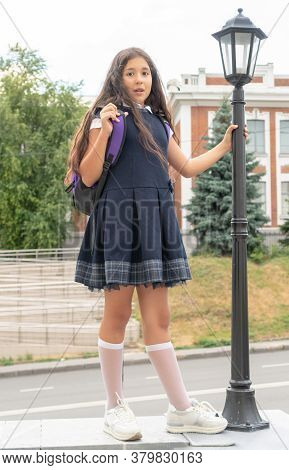 A Charming Girl With Long Curly Dark Hair In A School Uniform . Back To School. Vertical Photo.