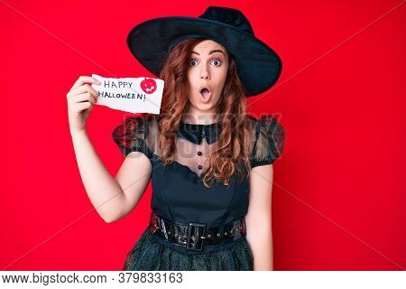 Young beautiful woman wearing witch costume holding happy halloween message paper scared and amazed with open mouth for surprise, disbelief face