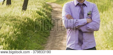 The Groom In A Purple Shirt And Tie Stands On A Path In The Forest. Folded His Hands On His Chest. B