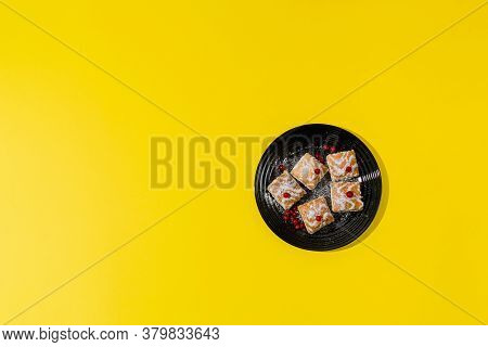 Gourmet French Pastries Decorated With Red Currant Berries In A Black Plate On A Yellow Background.