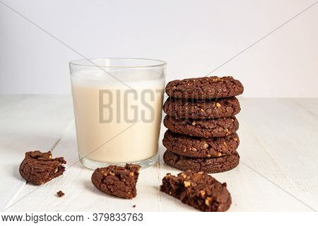 Stuck Of Chocolate Brownie Cookies And Glass Of Coconut Milk On Wooden Background. Homemade Pastry