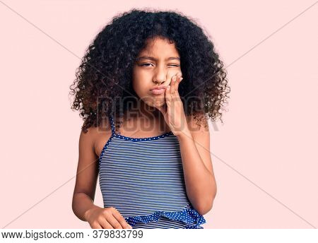 African american child with curly hair wearing swimwear touching mouth with hand with painful expression because of toothache or dental illness on teeth. dentist