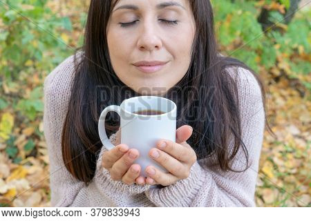 Middle-aged Woman Eyes Closed With Pleasure Holding Mug Of Hot Tea In A Hand In The Autumn Forest. C
