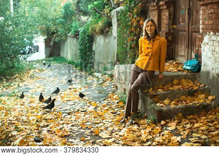 Woman in jacket and blu bag sits on the porch with maple leaves in the autumn day.