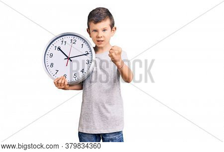 Cute blond kid holding big clock annoyed and frustrated shouting with anger, yelling crazy with anger and hand raised