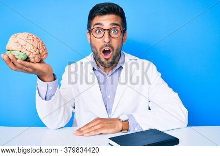 Young hispanic man sitting at the table wearing doctor coat holding brain scared and amazed with open mouth for surprise, disbelief face
