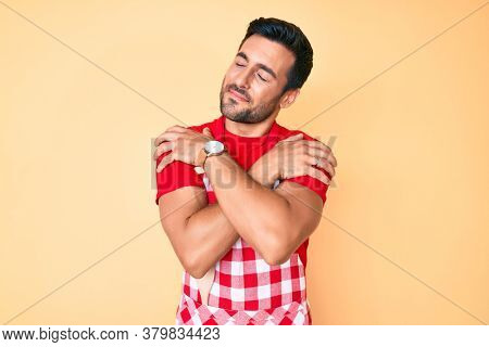 Young hispanic man wearing professional baker apron hugging oneself happy and positive, smiling confident. self love and self care