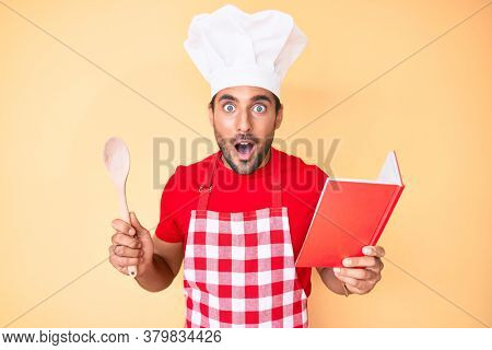 Young hispanic man wearing professional baker apron reading cooking recipe book afraid and shocked with surprise and amazed expression, fear and excited face.