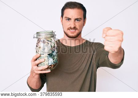 Young handsome man holding jar with savings annoyed and frustrated shouting with anger, yelling crazy with anger and hand raised