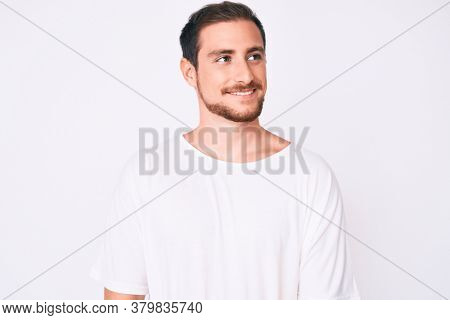 Young handsome man wearing casual white tshirt looking away to side with smile on face, natural expression. laughing confident.