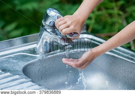 Baby Try To Turn Off Water Faucet But Water Still Leak. A Child Hand Turning Off The Tap. Save Water