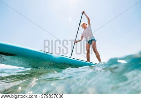 Water Surface-level View Angle To The Smiling Blonde Teenager Boy Rowing Stand Up Paddle Board. Acti