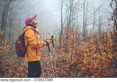 Dressed Bright Orange Jacket Young Female Backpacker Enjoying The Nature. She Walking In Autumn Fogg