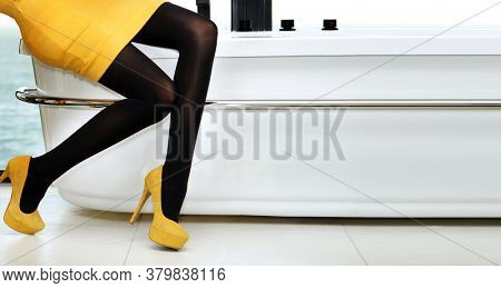 Fashion women clothes. Slender legs. Style. Yellow dress and yellow shoes. Bathroom. A party