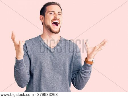 Young handsome caucasian man wearing casual winter sweater crazy and mad shouting and yelling with aggressive expression and arms raised. frustration concept.